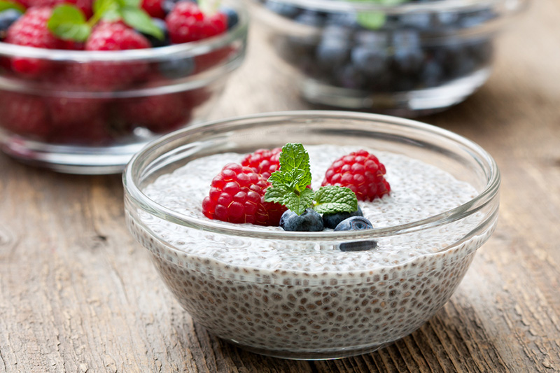 chia pudding with raspberries and blueberries in a glass bowl. An excellent s fresh berries on old wooden background